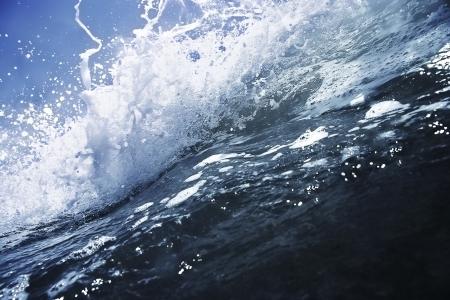mare agitato: Grande onda blu profondo rottura con spuma bianca, close up.