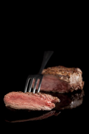 rare: delicious beef steak with fork on black background