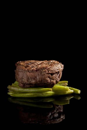 beef steak with beans on black background Stock Photo - 9489162