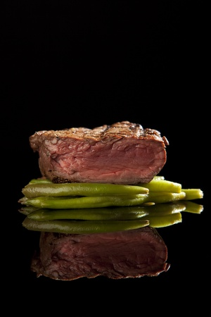 medium rare beef steak with beans on black background Stock Photo - 9489167