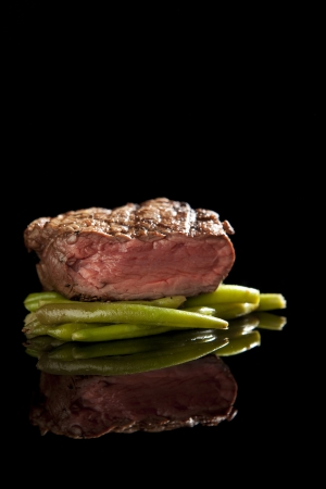 beef steak on black background with beans. Stock Photo - 9489165