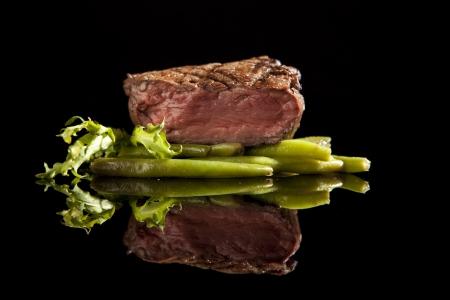 steak cru: steak de b?uf avec salade et haricots sur fond noir.