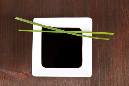 soy sauce: Soy sauce in white square bowl in dark wooden background with chive. Sushi concept.