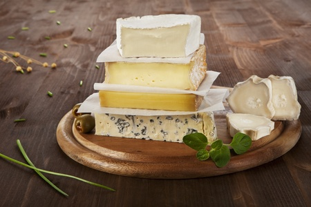 wood agricultural: Various cheese sorts on wooden board with olives, wheat and chive.