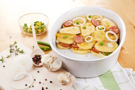 Fresh potatoes slices with fresh vegetables and sausage prepared for baking in bowl on wooden table. Stock Photo - 9553050