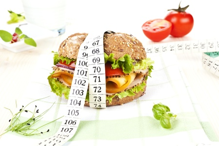 Sandwich with fresh vegetables and cheese and measuring tape wrapped around it on table with fresh herbs. Stock Photo