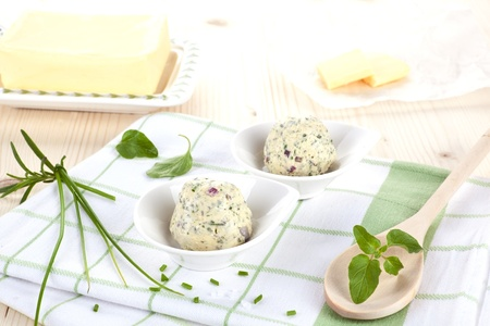Butter and herbal butter with fresh herbs basil and chive on kitchen towel on wooden table. Dairy products. Stock Photo
