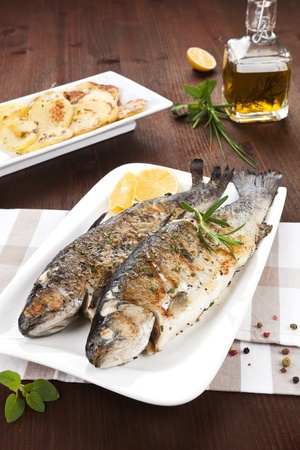 Two grilled trouts on white plate with lemon pieces, potatoes and olive oil on kitchen towel on wooden table. photo