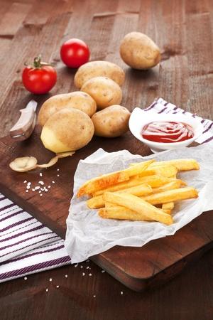 stile country: Patatine fritte su tavola di legno con patate e pomodori in background. Stile country.