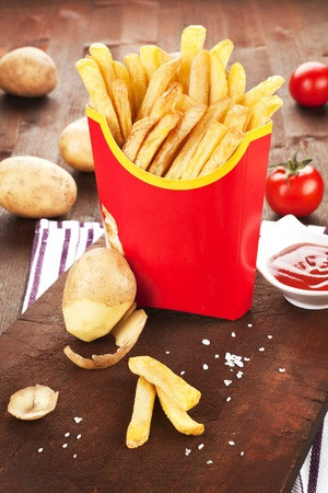French fries in fast food paper bag. Potatoes, tomatoes and ketchup in background. Stock Photo - 9617709