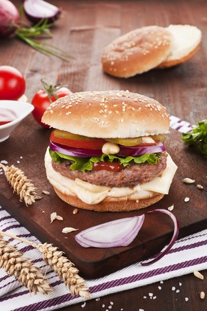 beef burger: Fresh cheeseburger on wooden board decorated with fresh vegetables and wheat. Stock Photo