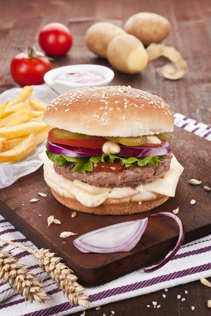 burger and fries: Country style hamburger on wooden board with potatoes, onions and chips.