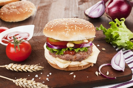 Big country style hamburger with tomatoes, onions on dark wooden cutting board.  photo