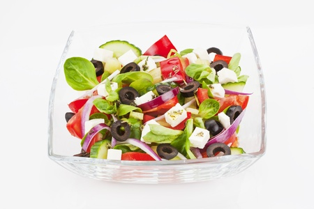 salad dressing: Fresh salad in glass bowl isolated on white.