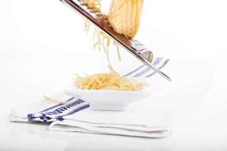Fromage râpé tombant dans un bol blanc sur une serviette isolé sur fond blanc. Banque d'images