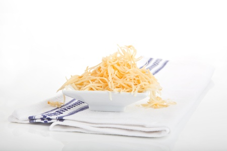 Grated cheese in white bowl on kitchen towel isolated on white background.  photo