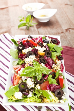 Colorful fresh salad with feta, goat cheese, olives, tomatoes and arugula. photo
