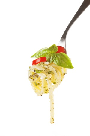 Pasta with tomato, pesto and fresh basil on fork isolated on white.  photo