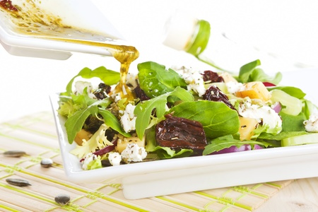 Pouring olive oil dressing on fresh goat cheese salad in white plate.  photo