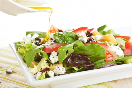 Pouring olive oil on fresh goat cheese salad with dried tomatoes in white plate.   photo