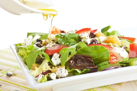Fresh goat cheese salad with fresh vegetables and olive oil. photo