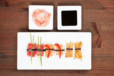 soy sauce: Delicious nigiri sushi on white plate. Ginger and soy sauce in white bowl.