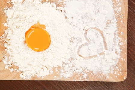 Flour and yolk on wooden board on brown table. Baking background. Stock Photo - 9835187
