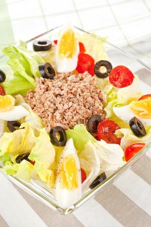Culinary tuna salad in glass bowl. Light summer salad. photo