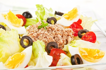 Tuna salad with olives, eggs and tomatoes close up. Summer food. photo