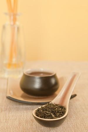 Black tea leaves on spoon, tea in tea bowl in background. photo