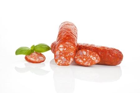 salami: Deliciosa salchicha aislado en blanco con hierbas frescas. Foto de archivo