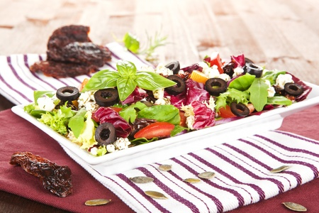 Delicious vegetable mix salad on white plate with dried tomatoes and seeds. photo