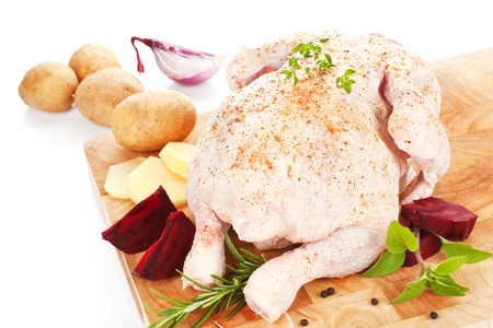 Delicious raw chicken on wooden board with fresh vegetable and herbs prepared for cooking. Stock Photo