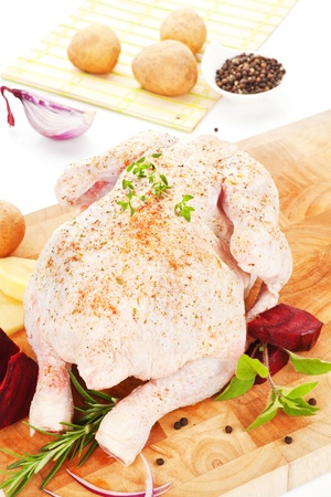 Luxurious raw chicken with fresh potatoes, beet, spices and fresh herbs. Delicious poultry background. photo