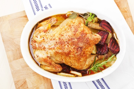 Luxurious golden baked chicken in white oval baking dish prepared for eating. Top view.  photo