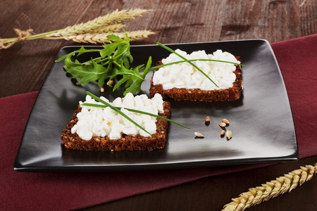 Two slices on black whole wheat bread with cottage cheese and fresh chive and arugula on black plate. Healhty eating background. photo