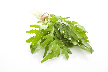 Fresh arugula leaves close up isolated on white background. Aromatic culinary herbs.