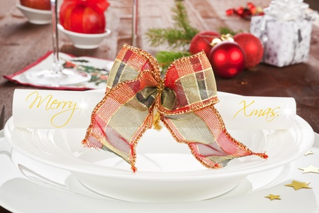 Christmas table with white plate, copy space, stars and christmas balls. Traditional red and green color christmas table. photo