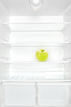 One apple in open empty white refrigerator. Weight loss diet concept.