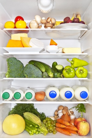 Full fridge of fruits, vegetables and diary products. Fresh healthy fitness eating concept.