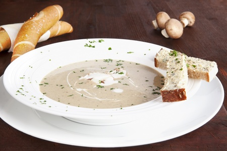 Champignon mushroom cream soup in white plate with pastry on dark wooden background. Culinary eating. photo