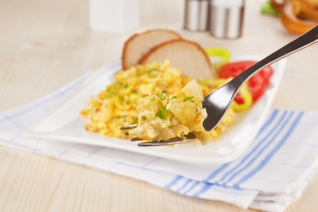 Culinary breakfast. Scrambled eggs on fork, pastry, salt and pepper shaker in background. Breakfast concept. photo