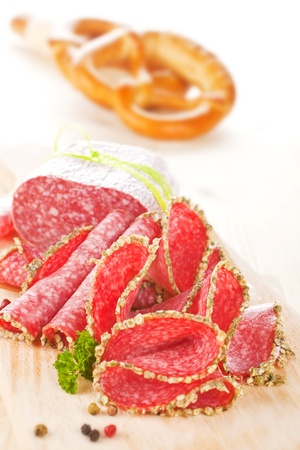 Salami slices on wooden board with fresh herbs and pepper corns. Pastry in background. Stock Photo - 10599989
