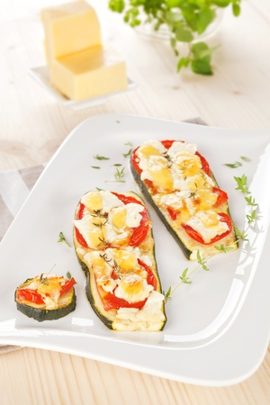 Delicious baked zucchini slices with tomato, cheese and thyme. Culinary vegetarian light eating. photo