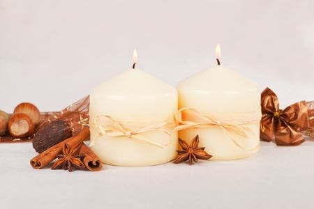Beautiful traditional christmas still life with burning candles, almond, nuts. ribbon and brown decoration. photo