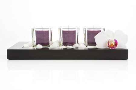 Zen still life with purple candles, white stones and orchid blossom on white background. Zen concept photo