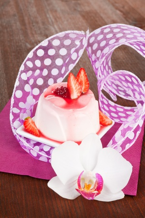 Delicious pudding with fresh strawberries and cream decorated with orchid on purple and wooden background. Culinary sweets concept. photo