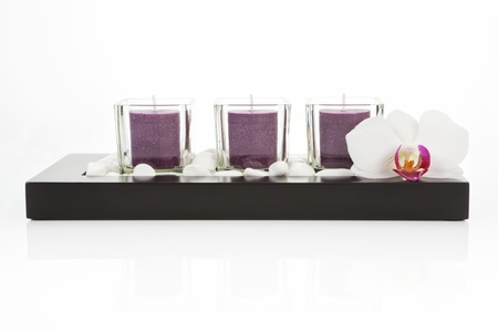 Zen still life with pruple candles, white stones and orchid blossom on white background. Zen concept photo