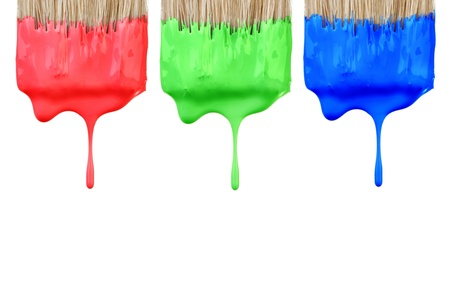 Red, green and blue paint dropping from brush isolated on white background. Graphic design creativity concept. photo