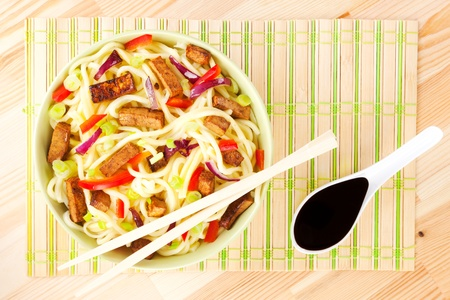 Noodles with tofu and vegetable, chopsticks and soy sauce. Asian food concept. photo
